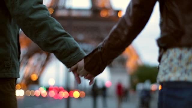 vidéos et rushes de cu. jeune couple se tient la main à l'approche de la tour eiffel lors d'une escapade parisienne romantique. - paris