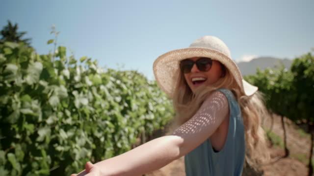 young couple holding hands in vineyard - azienda vinicola video stock e b–roll