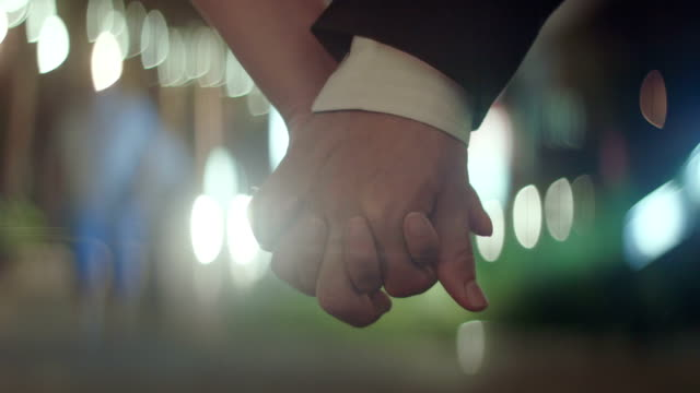 Young couple holding hands together ,close up video