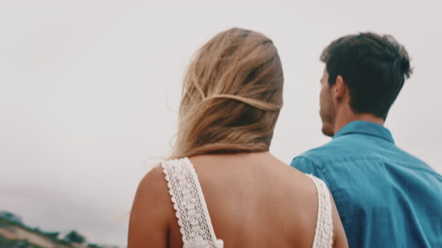 Young couple holding hands while walking at beach