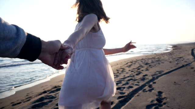Young couple holding hands woman leading boyfriends walking towards sunset video