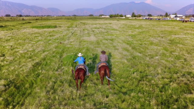 Young Couple Horseback Riding Young Couple Horseback Riding in Western America prairie stock videos & royalty-free footage