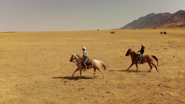 Young Couple Horseback Riding Young Couple Horseback Riding in Western America rancher stock videos & royalty-free footage