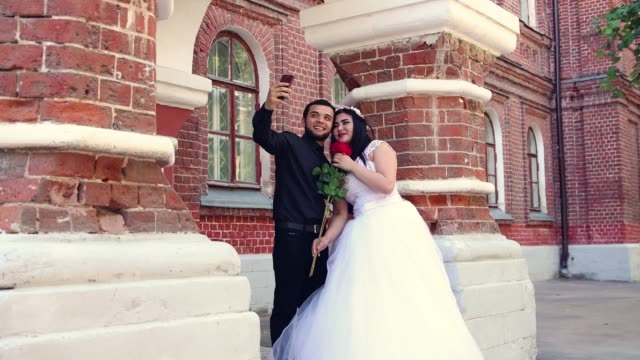 a young couple hugs and is photographed on a smart phone. - young couple wedding friends video stock e b–roll