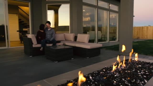 Jeunes couples dans la cour arrière à la cheminée extérieure - Vidéo