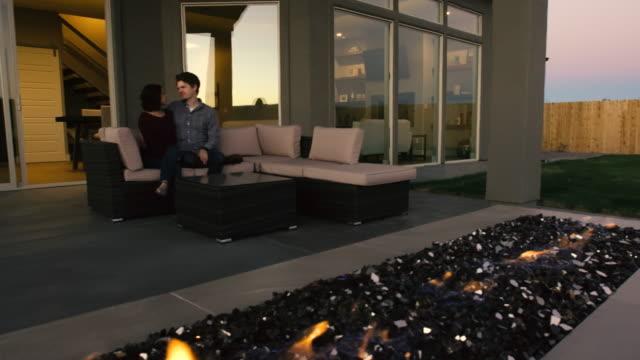 裏庭の屋外の暖炉での若いカップル - パティオ点の映像素材/bロール
