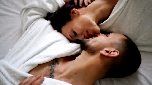 Young couple in bed Young couple in love kissing and cuddling on the bad. young couple stock videos & royalty-free footage