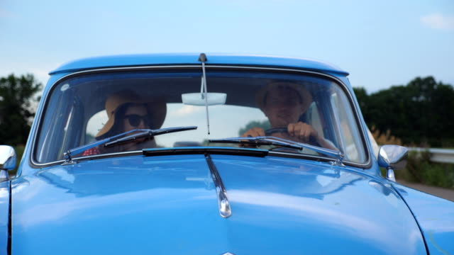 Young couple in hats riding in vintage car at summer travel. Man and woman sitting at the front seat of old retro car and talking during ride. Concept of road trip at holidays . Slow motion Close up