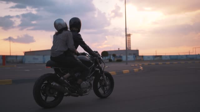 vídeos de stock e filmes b-roll de young couple in helmets riding on motorcycle in city during sunset, slow motion - helmet motorbike