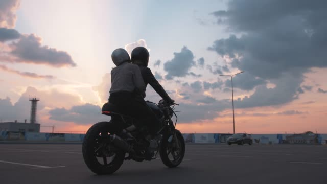 vídeos de stock e filmes b-roll de young couple in helmets riding on motorcycle in city with beautiful sunset sky background, slow motion - helmet motorbike