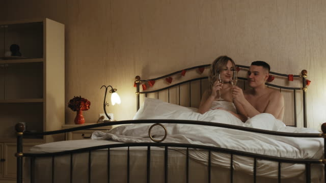 Young couple in love drink champagne in bed