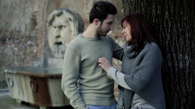 młoda para w miłości w rzymie :  zaangażowanie, pieszczoty, przylega, romantyczne partnerów - część ciała zwierzęcia filmów i materiałów b-roll
