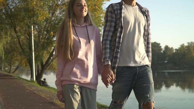 Young couple in love spend time together Happy couple walks near the lake. Adult man and lady walk in the park holding hands. Lovers spend time together short length stock videos & royalty-free footage