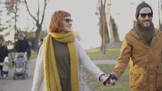 夕暮れ時の公園を歩いて愛の若いカップル。 - 対面点の映像素材/bロール