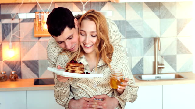 young couple in morning with pancakes - pancake video stock e b–roll