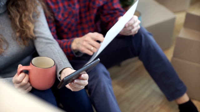 Young couple in new apartment looking at phone plan of arrangement of furniture