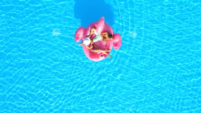 stockvideo's en b-roll-footage met luchtfoto top down: jong koppel in zwembroek nippen van cocktails op flamingo floatie - opblaasband
