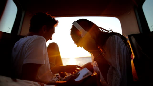 Video Young couple in the car trunk on vacation.Sea and sunset in background.