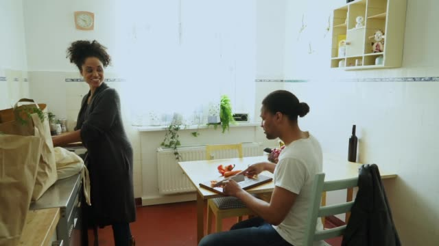 Young couple in their kitchen Berlin couple preparing and eating vegetables in their kitchen. kitchen utensil stock videos & royalty-free footage