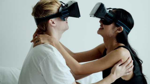 Young couple in VR 3-D glasses having fun on bed