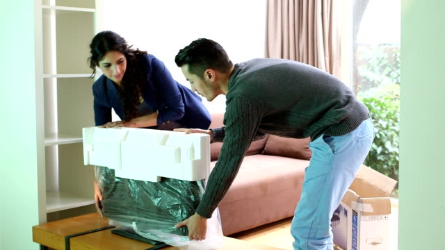 Young couple installing new television in living room