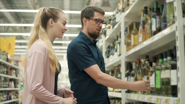 Young couple is discussing wine in a department of supermarket