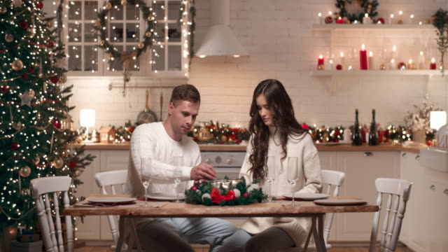 A young couple is preparing for the arrival of guests for Christmas dinner. They set the Christmas table in the living room, light candles. A young couple is preparing for the arrival of guests for Christmas dinner. They set the Christmas table in the living room, light candles. russian ethnicity stock videos & royalty-free footage