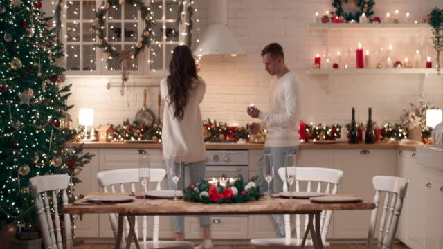 una giovane coppia si prepara all'arrivo degli ospiti per la cena di natale. hanno messo il tavolo di natale nel soggiorno, accendere candele. - christmas table video stock e b–roll