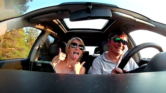 Young couple is riding a car in a sunny day video