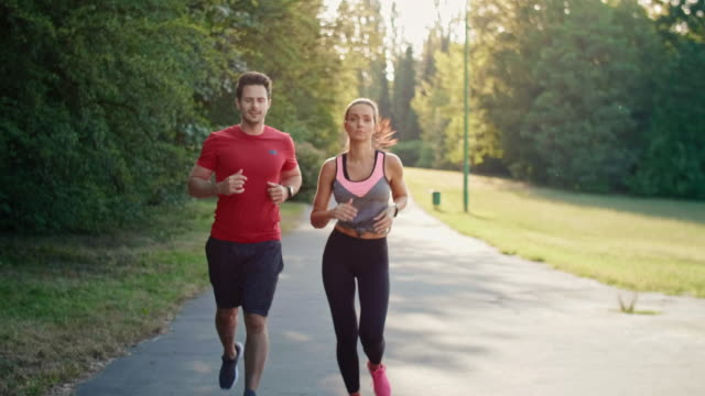Young couple jogging during sunny afternoon