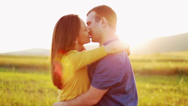 Giovane coppia Baciare al tramonto - video