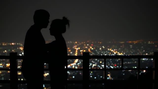 Young couple kissing on the background of the city at night urban scene, 4k(UHD) video