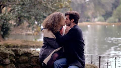 stockvideo's en b-roll-footage met jong paar dat passionalety bij park bij het meer kust - alleen volwassenen