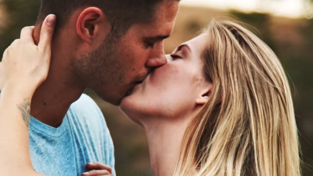 Young couple kissing while hiking Close-up of boyfriend kissing girlfriend. Male and female are enjoying vacation. Carefree couple is hiking. heterosexual couple stock videos & royalty-free footage