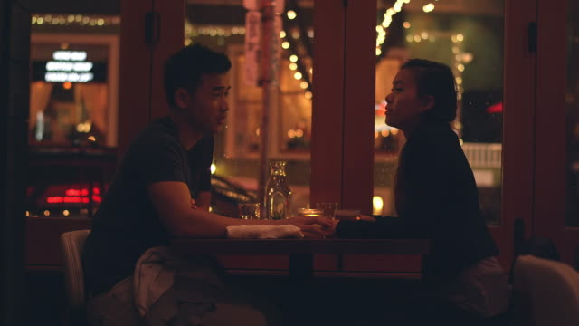 A young couple laughing on a romantic dinner date, with city lights behind them video