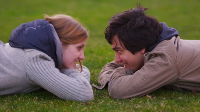 Young couple laying in grass talking video