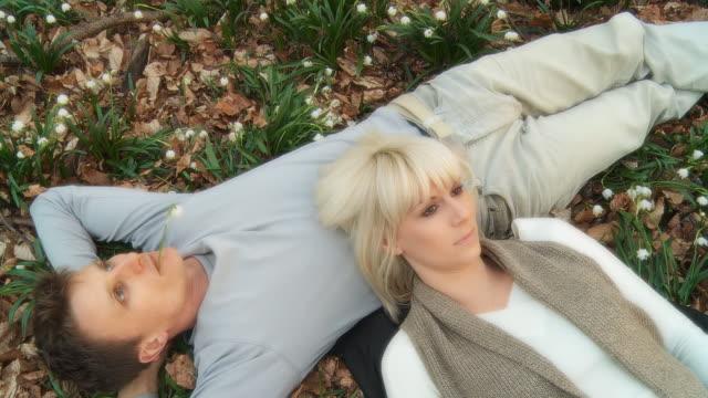 vidéos et rushes de hd: jeune couple main dans la forêt de printemps - allongé sur le dos