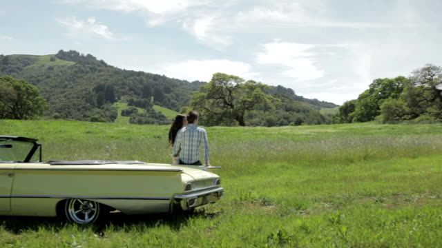 Young couple leaning on vintage car in nature video