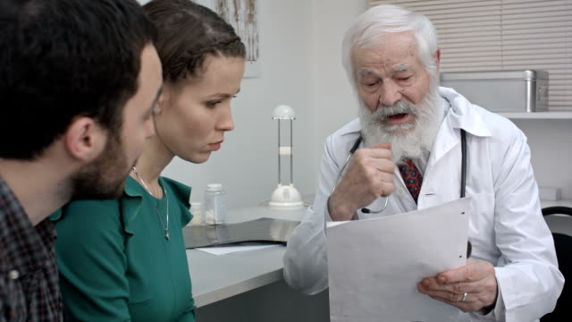Young couple listening to mature doctor who tells them results of the research video