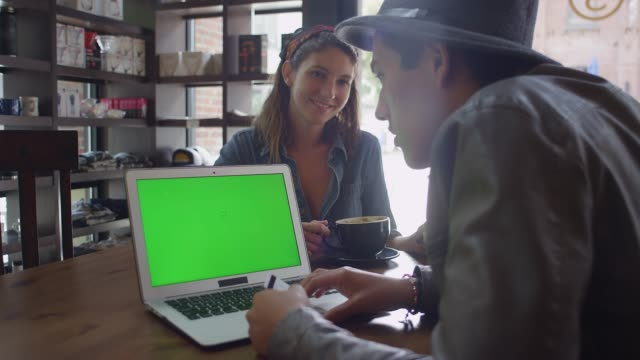 A young couple looking a laptop in a coffee shop, green screen