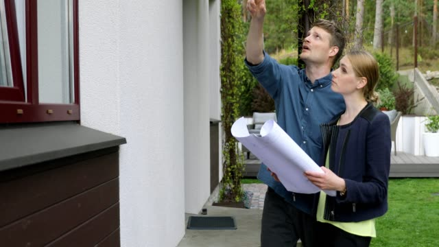 young couple looking at blueprints and doing inspection of new family house they want to buy young couple looking at blueprints and doing inspection of new family house they want to buy quality control stock videos & royalty-free footage