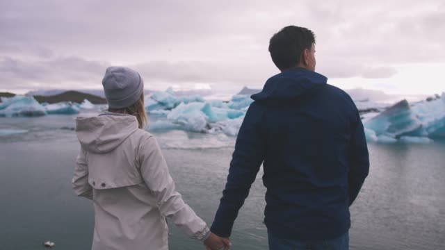 молодая пара глядя на озеро ледник jokulsarlon в исландии, кинематографический выстрел - ледник стоковые видео и кадры b-roll