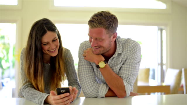 DOLLY SHOT: Young couple looking at pictures on smartphone video