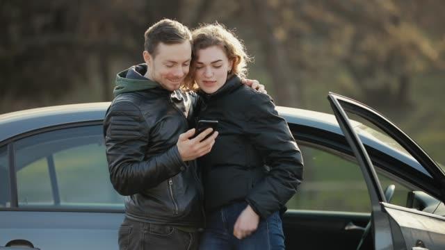 vídeos de stock, filmes e b-roll de jovem casal olhando para smartphone perto do carro - veículo terrestre