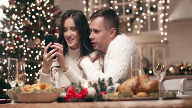 A young couple looks at photos on their smartphone at the Christmas table. While waiting for guests, they send Christmas greetings to parents and friends via phone. A young couple looks at photos on their smartphone at the Christmas table. While waiting for guests, they send Christmas greetings to parents and friends via phone. treedeo christmas stock videos & royalty-free footage