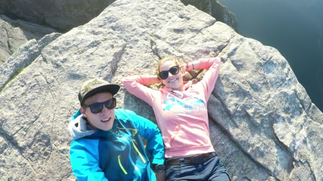 A young couple lying at the edge of Preikestolen (Pulpit Rock), Norway, overlooking Lysefjord. Wild camping in the nature. The sun starts to set. Dangerous place. The couple is having fun. Travel goal