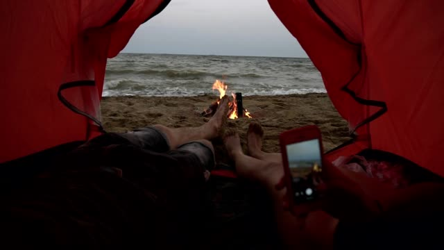 young couple lying inside of the red tent. close up footage of male and female legs. girl is making a phote of their feet using a smartphone. sea viewon the background - campeggio video stock e b–roll