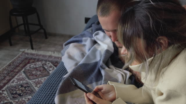 Young Couple Lying On Bed Using Smartphone. Couple addicted to social media networks spending time in bed together hugging and texting everyone on their smartphones