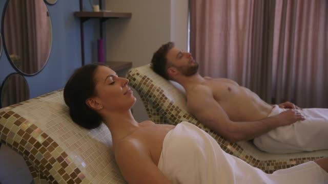 junges paar liegt auf den tepidariumbetten im spa - sun chair stock-videos und b-roll-filmmaterial