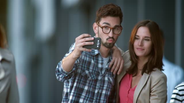 slo mo giovane coppia facendo selfie in città street - fare la lingua video stock e b–roll